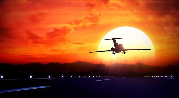 大きなジェット旅客機が離陸滑走路の上空を飛ぶ Premium写真
