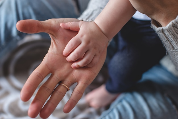 Big man's and small children's palms one on another. father's love and protection. succession of generations Premium Photo