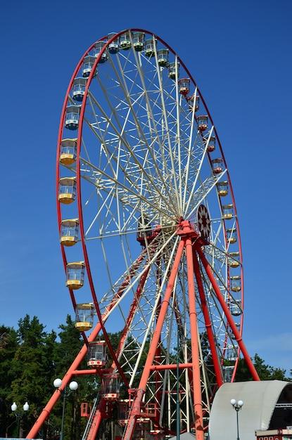 Big and modern multicolour ferris wheel on clean blue sky background Premium Photo