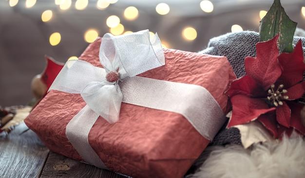 Grande rosso presente sopra le luci di natale bokeh in casa sulla tavola di legno. decorazione natalizia, magico natale Foto Gratuite