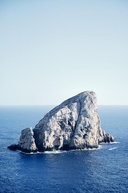 青い空と海の真ん中に大きな岩 無料写真