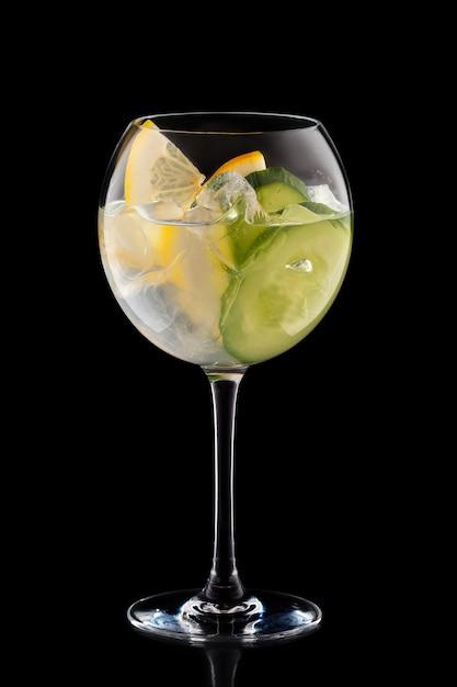 Big round wine glass with fresh cold lemonade isolated on black background Premium Photo