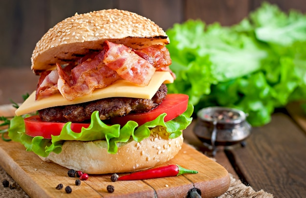 Big sandwich - hamburger burger with beef, cheese, tomato and fried bacon Free Photo
