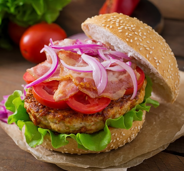 Big sandwich - hamburger burger with beef, red onion, tomato and fried bacon. Free Photo