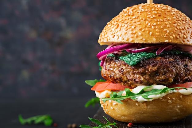 Big sandwich - hamburger burger with beef,  tomato, basil cheese and arugula. Premium Photo