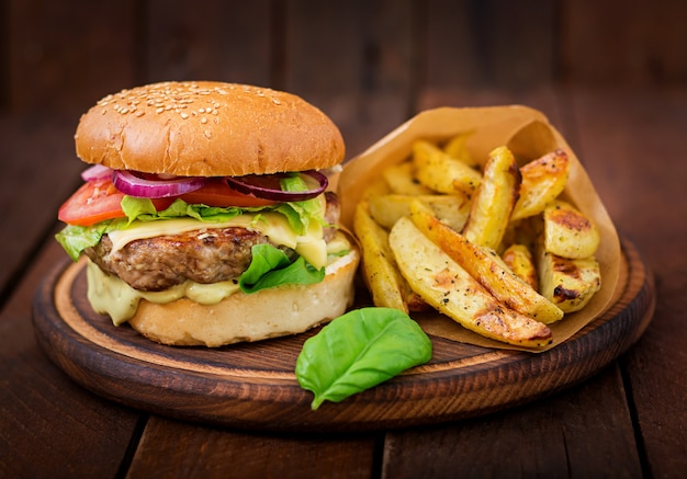 Big sandwich - hamburger with juicy beef burger, cheese, tomato,  and red onion on wooden table Free Photo