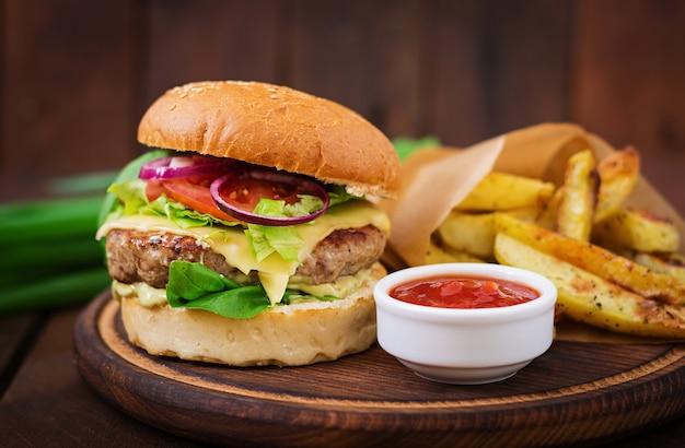 Big sandwich - hamburger with juicy beef burger, cheese, tomato, and red onion Premium Photo