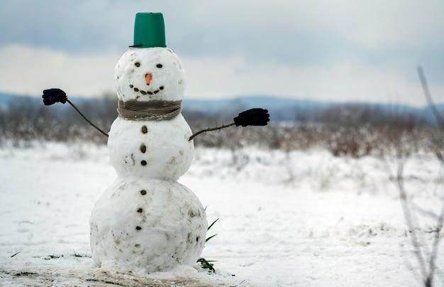Большой улыбающийся снеговик с ведром, шарфом и перчатками на белом снежном поле зимний пейзаж, размытые черные деревья и голубое небо копируют космический фон. . открытка с новым годом и рождеством. Premium Фотографии