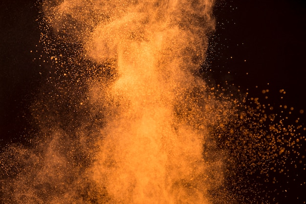 Big splash of orange makeup powder on dark background Free Photo
