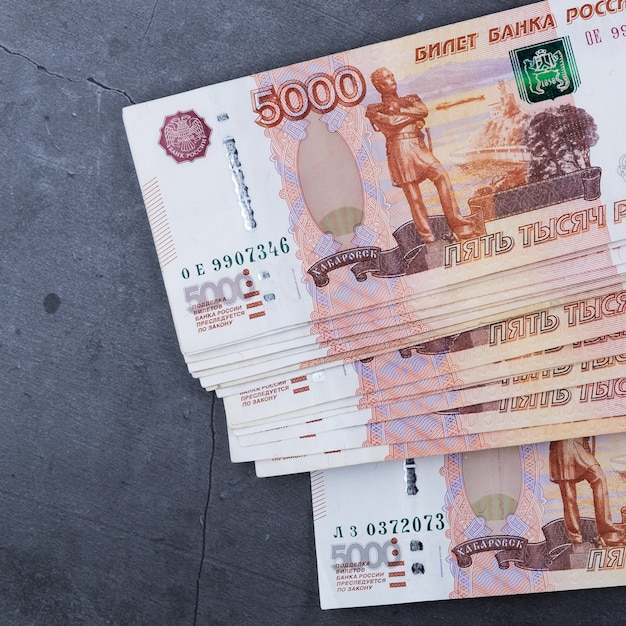 Big stack of russian money banknotes of five thousand rubles lying on a grey cement. Premium Photo