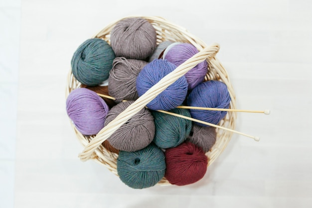 Big traditional basket with a variety of wood of yarns and knitting needles Premium Photo