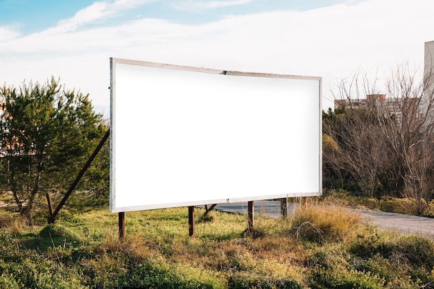 Big white billboard on green roadside Free Photo