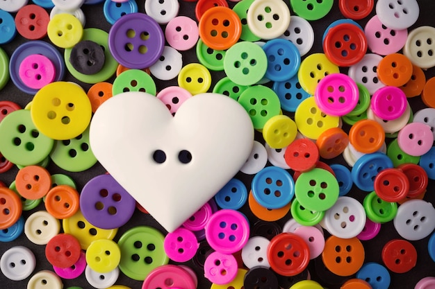 Big white heart button on small assorted colors buttons