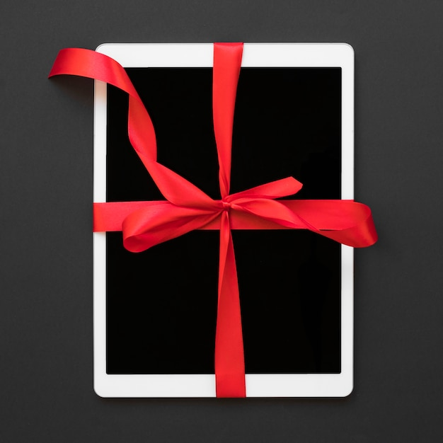 Big white tablet with red ribbon Free Photo