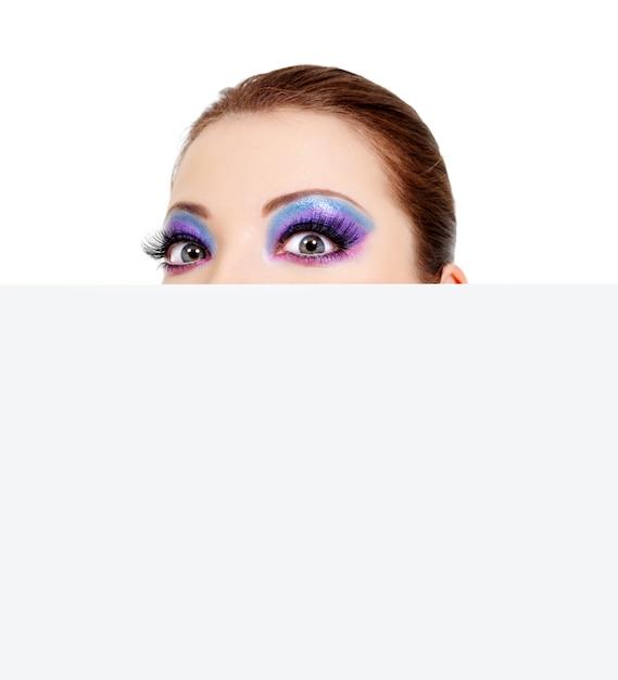 Grandi occhi da donna che guardano da una bandiera bianca vuota Foto Gratuite