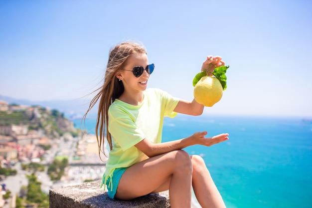 Big yellow lemon in hand in mediterranean sea and sky. Premium Photo