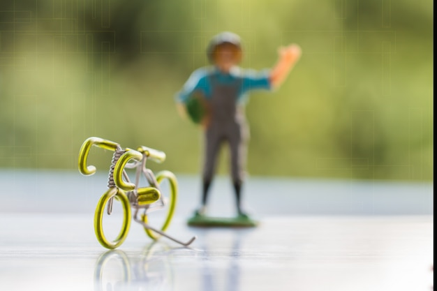 Bike and miniature farmer people standing ideas for save planet Premium Photo