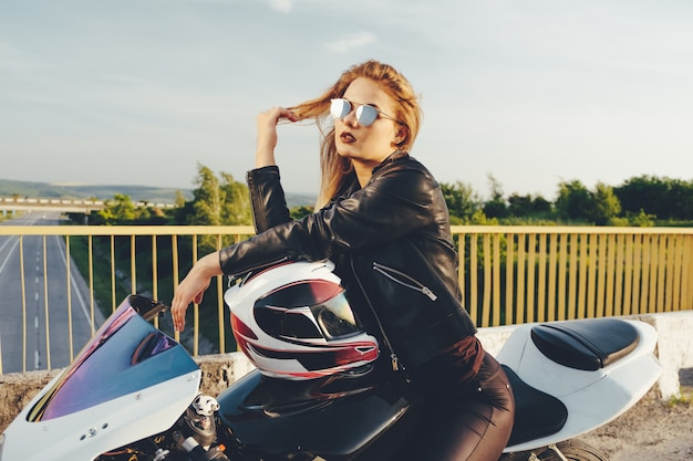 Biker girl in a leather clothes on a motorcycle Free Photo