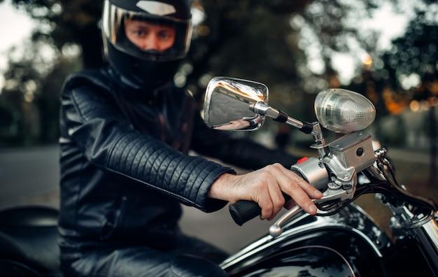 Байкер в шлеме позирует на мотоцикле, классический чоппер. винтажный велосипед, наездник и его двухколесный друг, образ жизни свободы, езда на велосипеде Premium Фотографии