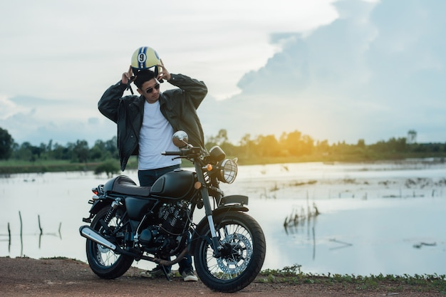 Biker man with his motorbike beside the natural lake and beautiful. Premium Photo