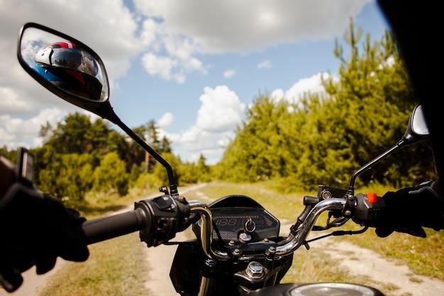 Biker riding motorbike on dirt road Free Photo