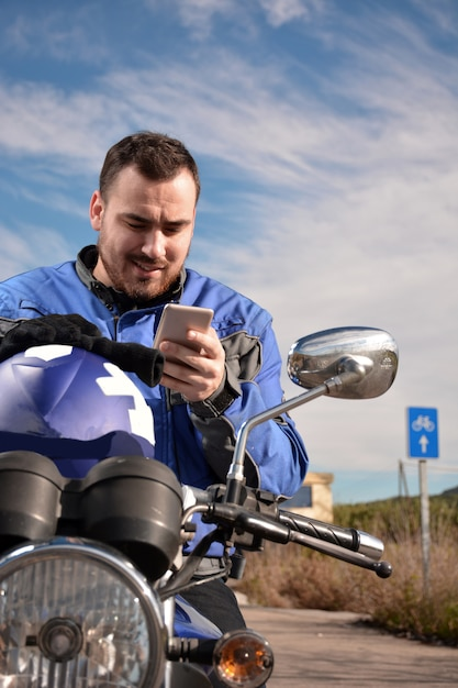 Biker talking by phone with his smarth phone Premium Photo