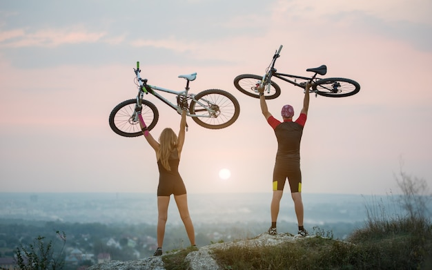 Bikers holding bikes high up in the sky on the top of a hill against magnificent sunset with blurred background. pink kinesio tape glued on the girl's hand. Premium Photo
