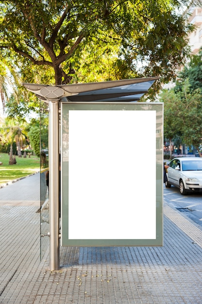 Billboard at bus stop in front of trees Free Photo