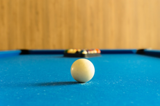 Billiards pool game. white ball on spot with set colours ball in background on blue table. Premium Photo