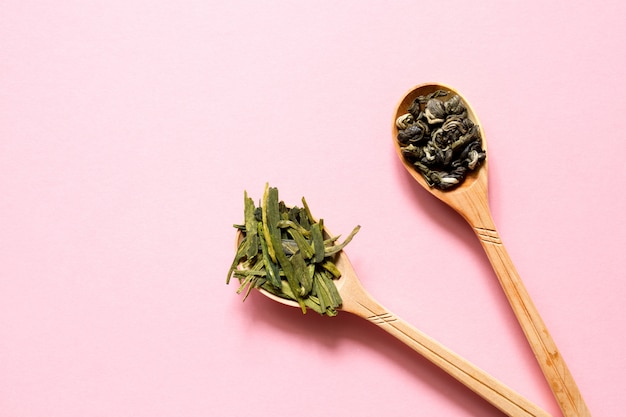 Biluochun and longjing. chinese leaf green tea in a spoon on a pink background. Premium Photo