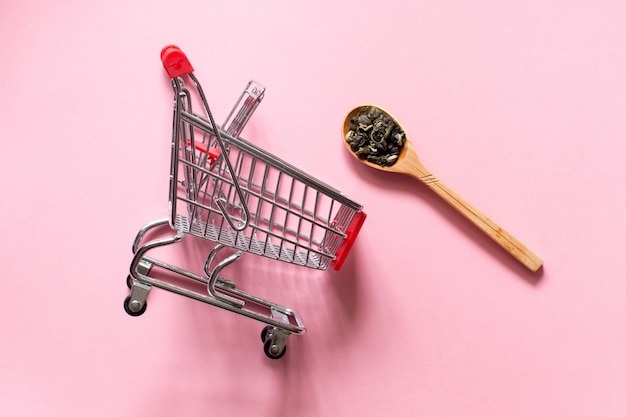 Biluochun and  shopping cart trolley.  chinese leaf green tea in a spoon on a pink background. Premium Photo