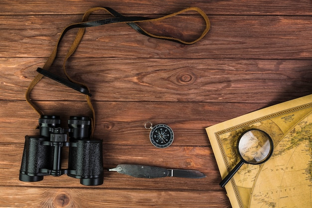 Binocular, compass, and knife with microscope on vintage map Free Photo