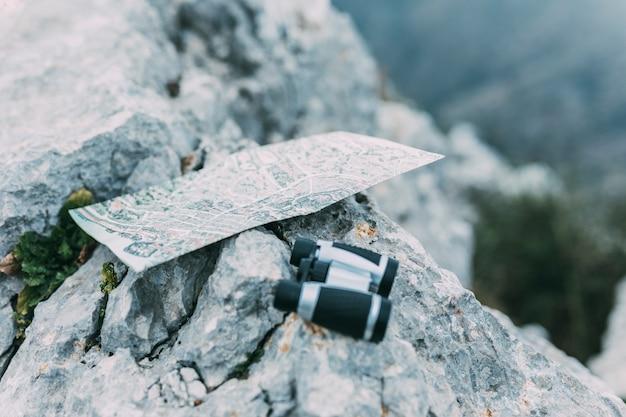 Binoculars and map on rock Free Photo