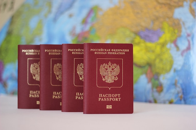 Biometric russian passports are in a row on the world map. Premium Photo