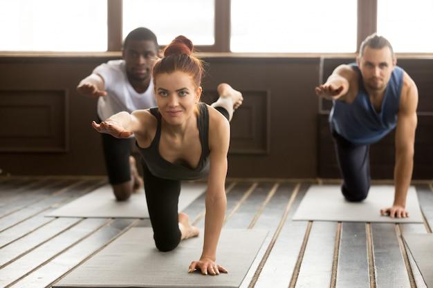 Группа спортивных людей в bird dog упражнение с инструктором Бесплатные Фотографии