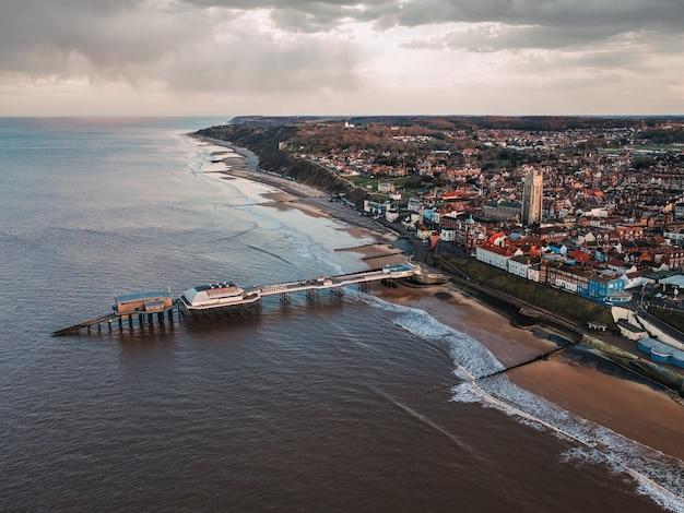 Panoramica della città, della spiaggia pubblica e del molo in una giornata uggiosa Foto Gratuite