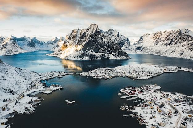 雪山のある水域の近くの海岸沿い町の鳥瞰写真 無料写真