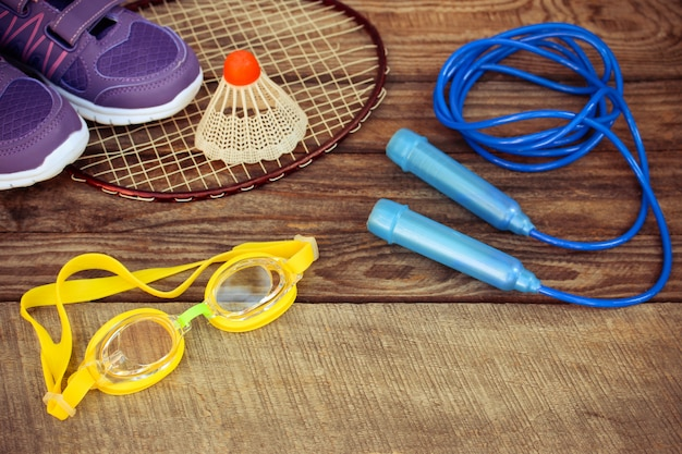 Birdie is on the racket, skipping rope, swimming goggles and sneakers on wooden background. Premium Photo