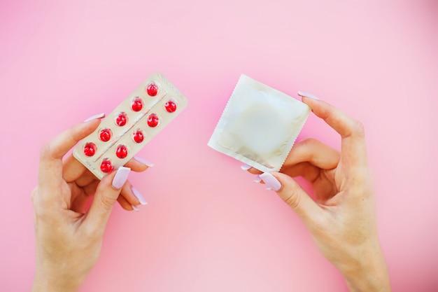 Birth control pills and an unwrapped condom. Premium Photo