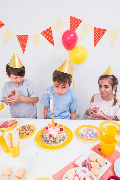 Birthday boy blowing candle with his friends standing behind cake Free Photo