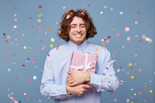 눈을 감은 생일 소년, 흰색 리본으로 묶인 선물 상자를 자신에게 누릅니다. 무료 사진