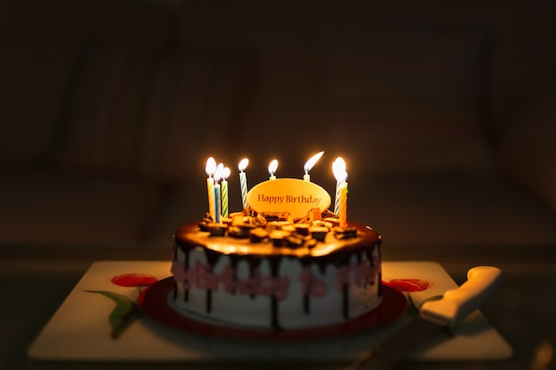 Birthday cake on black table with colorful candles lit. Premium Photo