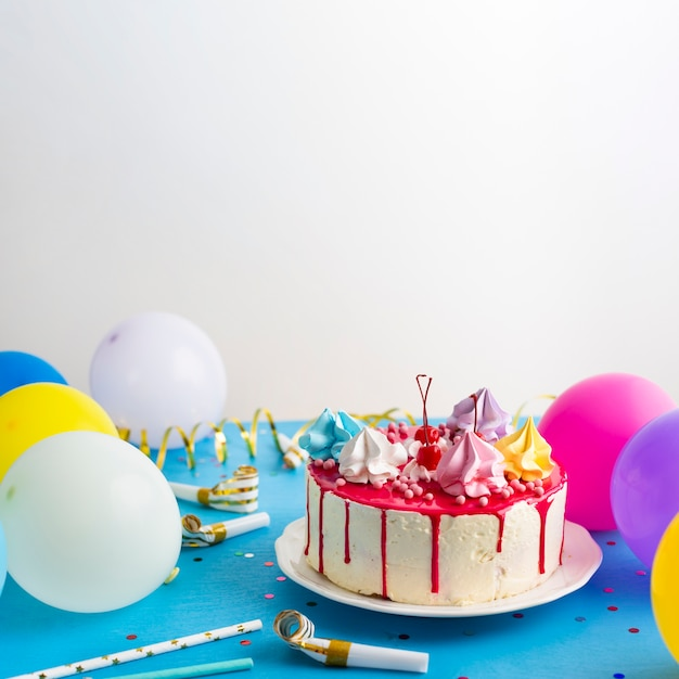 Birthday cake and colorful balloons Free Photo