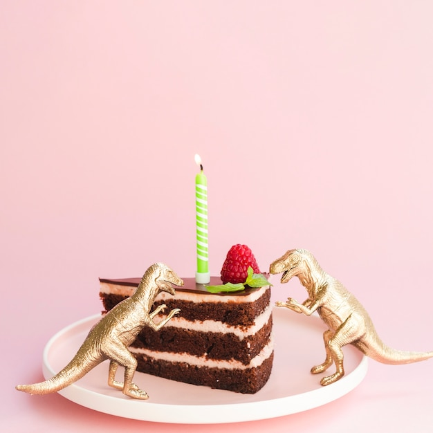 Torta di compleanno e dinosauri su sfondo rosa Foto Gratuite