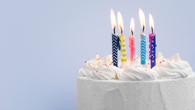 青色の背景にキャンドルで誕生日ケーキ Premium写真