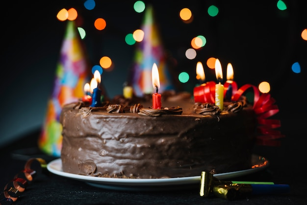 Birthday cake with an illuminated candle against light backdrop and party hat Free Photo