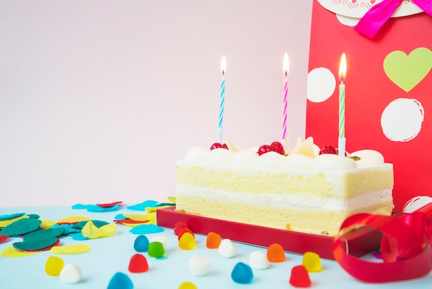 Birthday cake with lighted candles; candies and shopping bag Free Photo