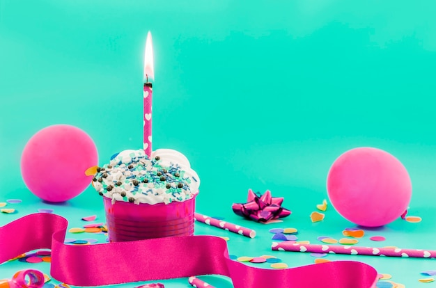 Birthday cupcake with candle and balloons Free Photo