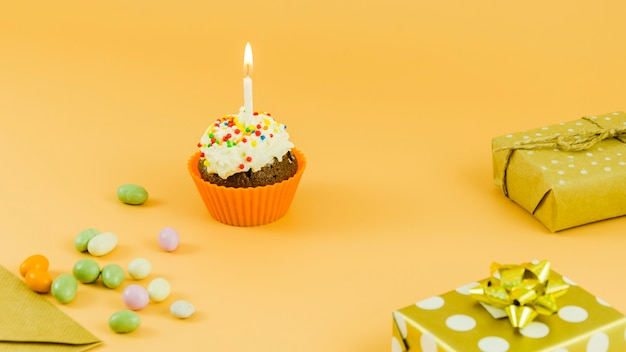 Birthday cupcake with candle and gifts Free Photo