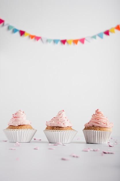 アイシングと花輪の誕生日カップケーキ 無料写真